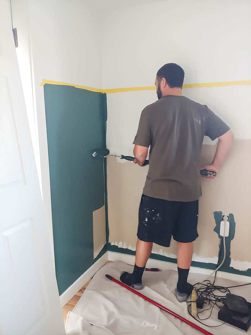 Painting the bottom part of the two tone walls with roller.