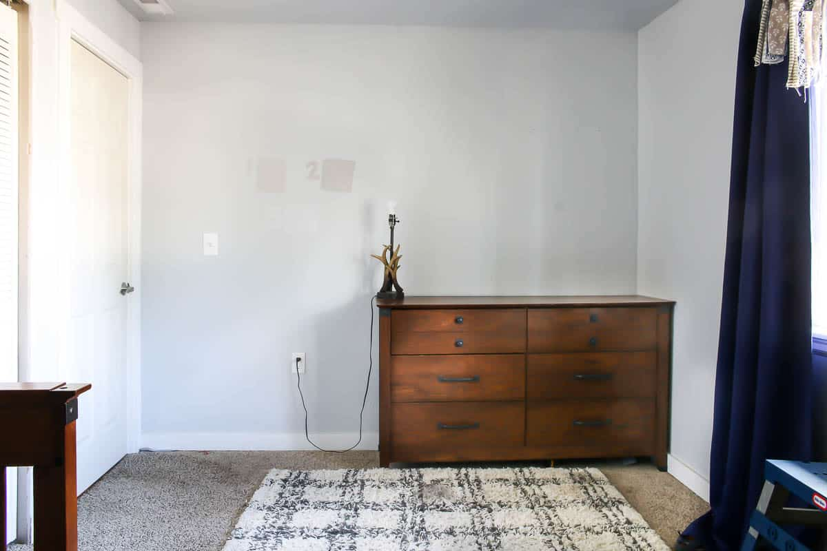 plain bedroom wall before makeover with a wooden dresser and a rug