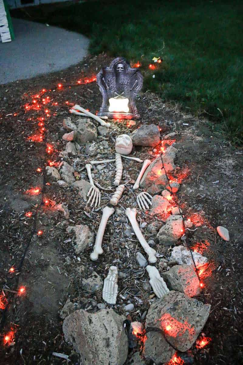 Fake skeletons scattered in a fake graveyard with red lights.