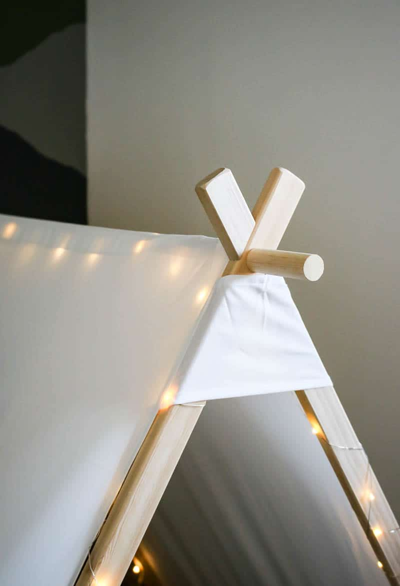 Upper part of the wooden nook made out a teepee tent with lights added for a boy's toddler room