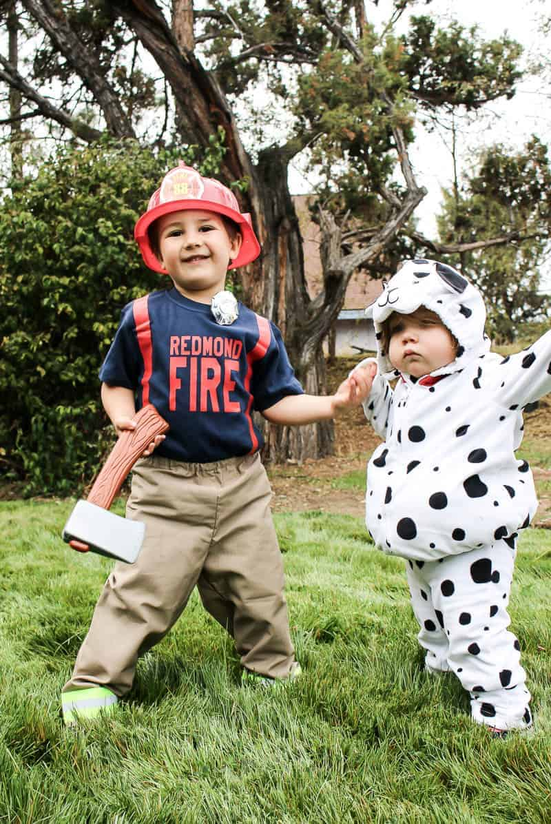 Toddler boy wearing fireman costume and toddler girl wearing Dalmatian dog costume to create a cute sibling costume idea for toddlers