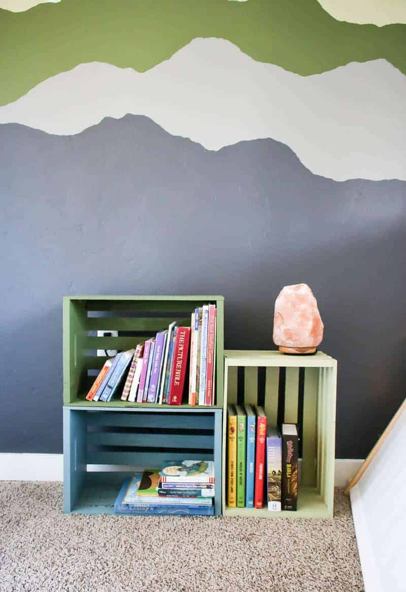 Painted wall behind the colorful painted wood crate bookshelves for toddler play room