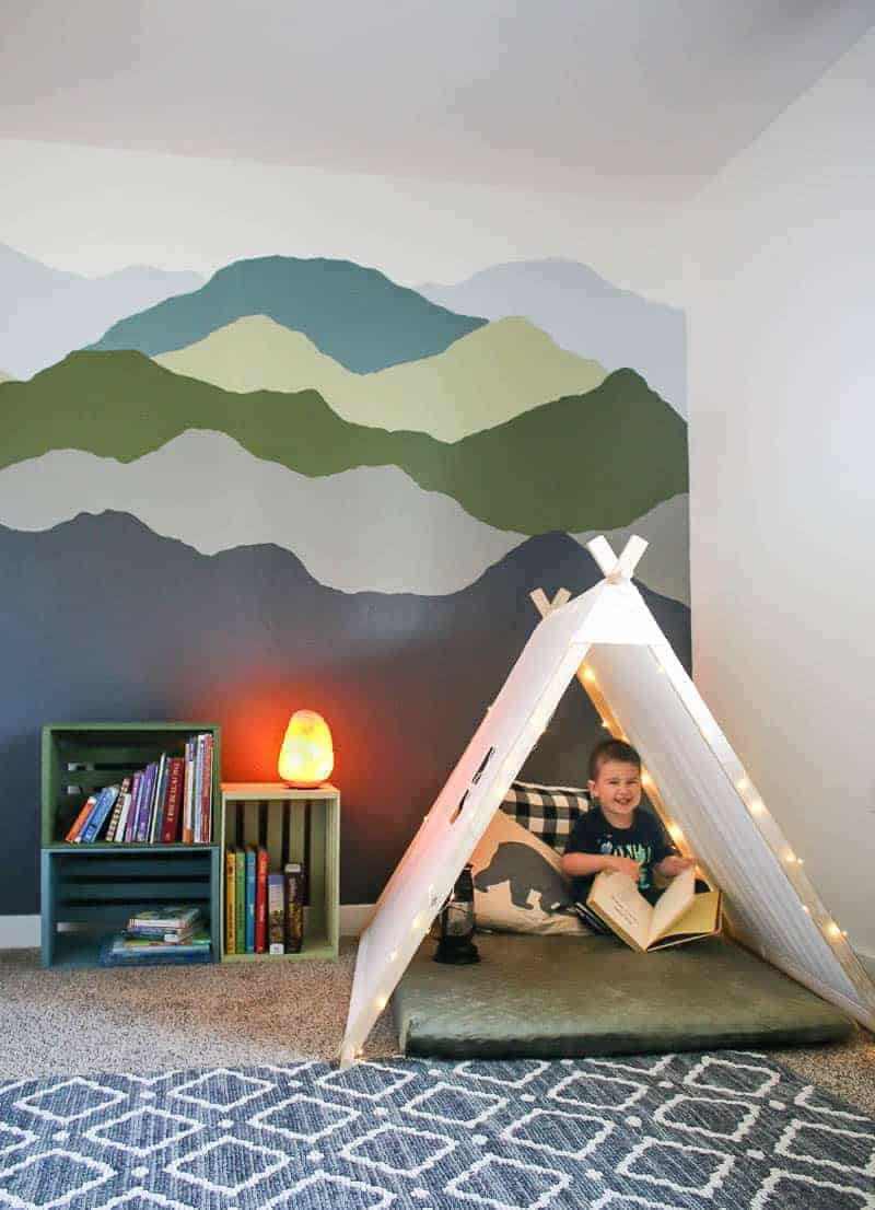Boy sitting in the cozy nook beside the colorful pallet bookshelves and mountain mural paint