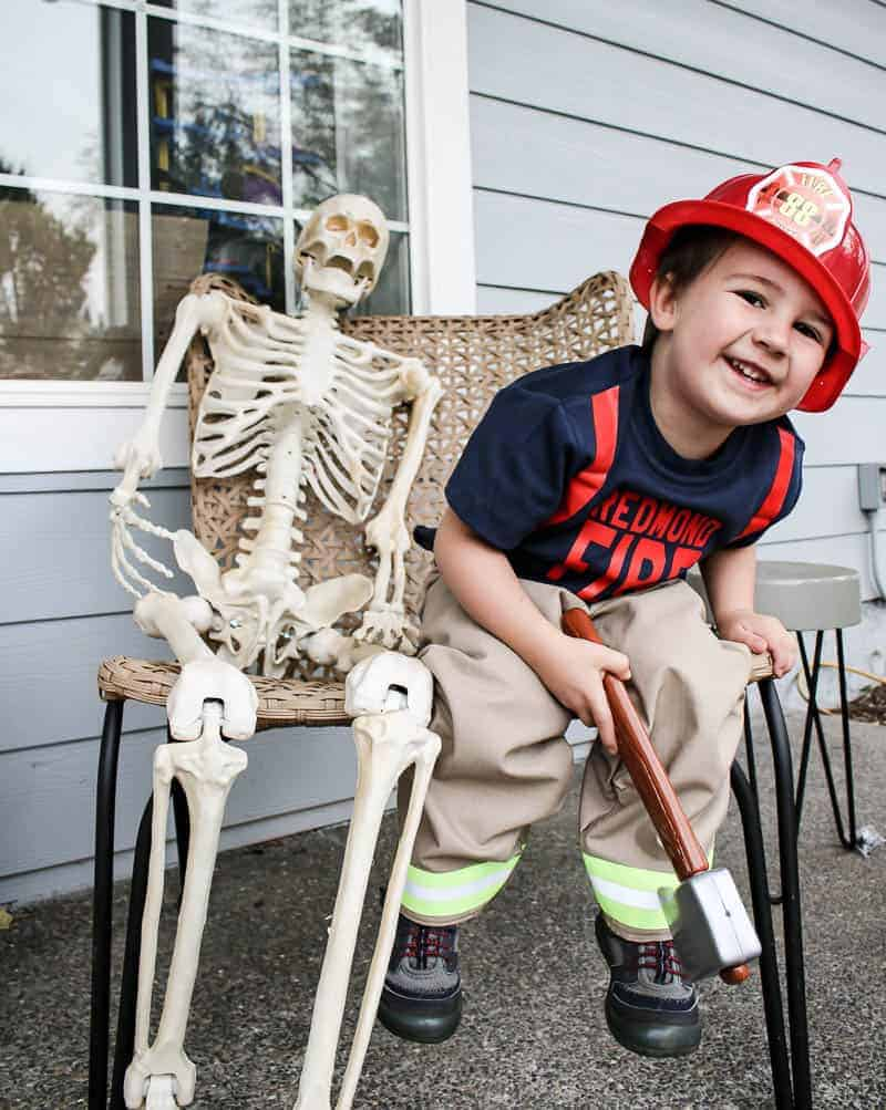 Toddler boy wearing firefighter costume for Halloween sitting on chair on front porch next to fake skeleton