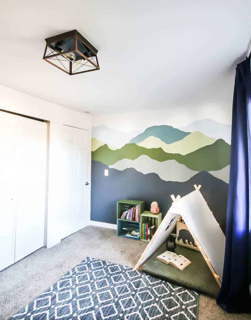 Full view of the nursery with mountain mural, barn chandelier, colorful shiplap book shelves and the DIY nook for the farmhouse kid bedroom