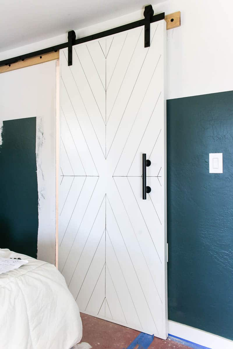 Full image of the built white modern barn door with x design hanging in bedroom