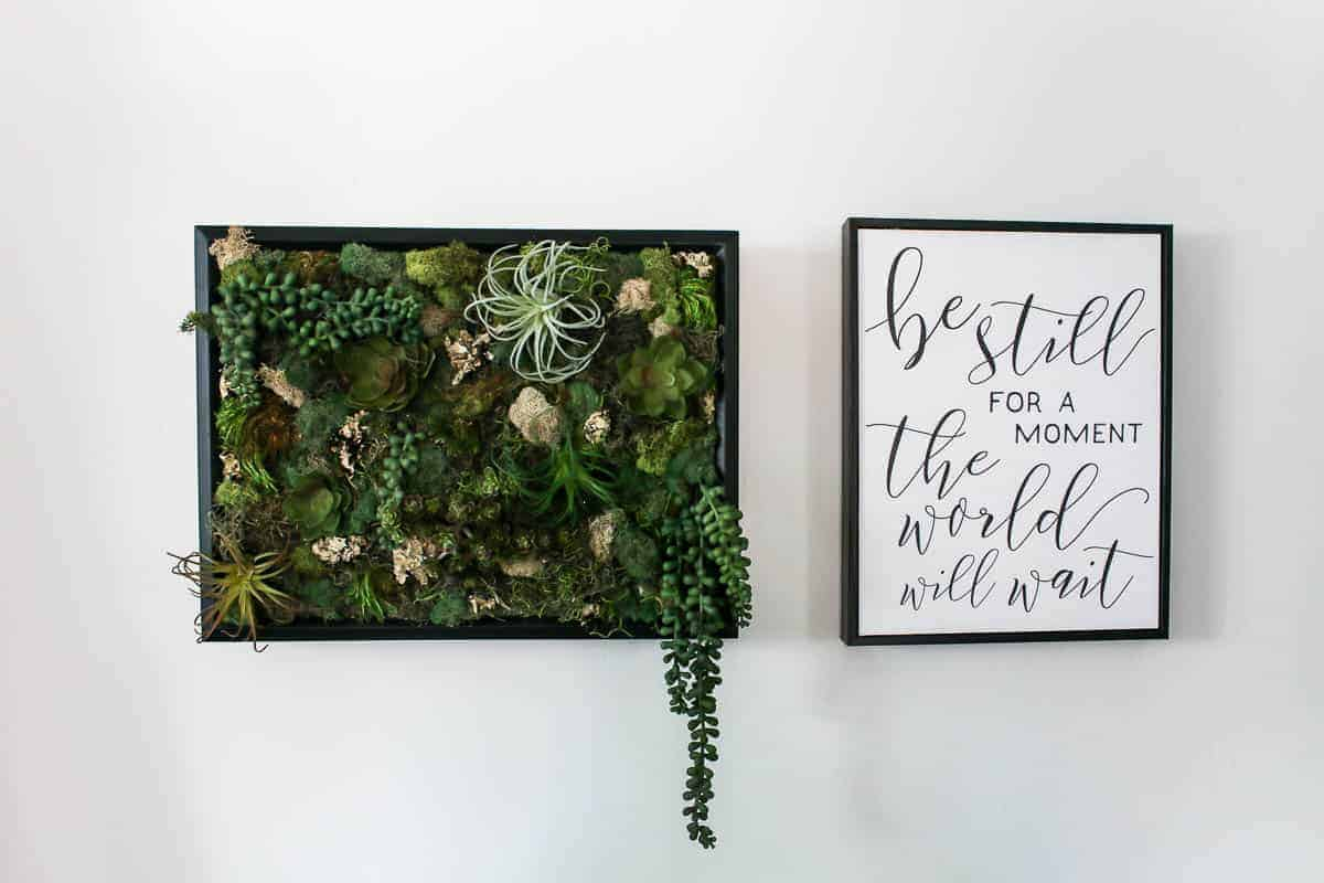 Wall decor shown on white wall with green faux succulents and moss in black frame as a vertical garden and black and white wall decor that says be still for a moment the world will wait
