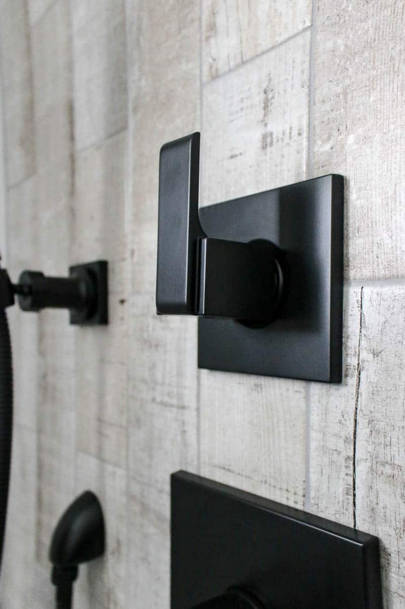 Black matte shower faucets against wood look tile