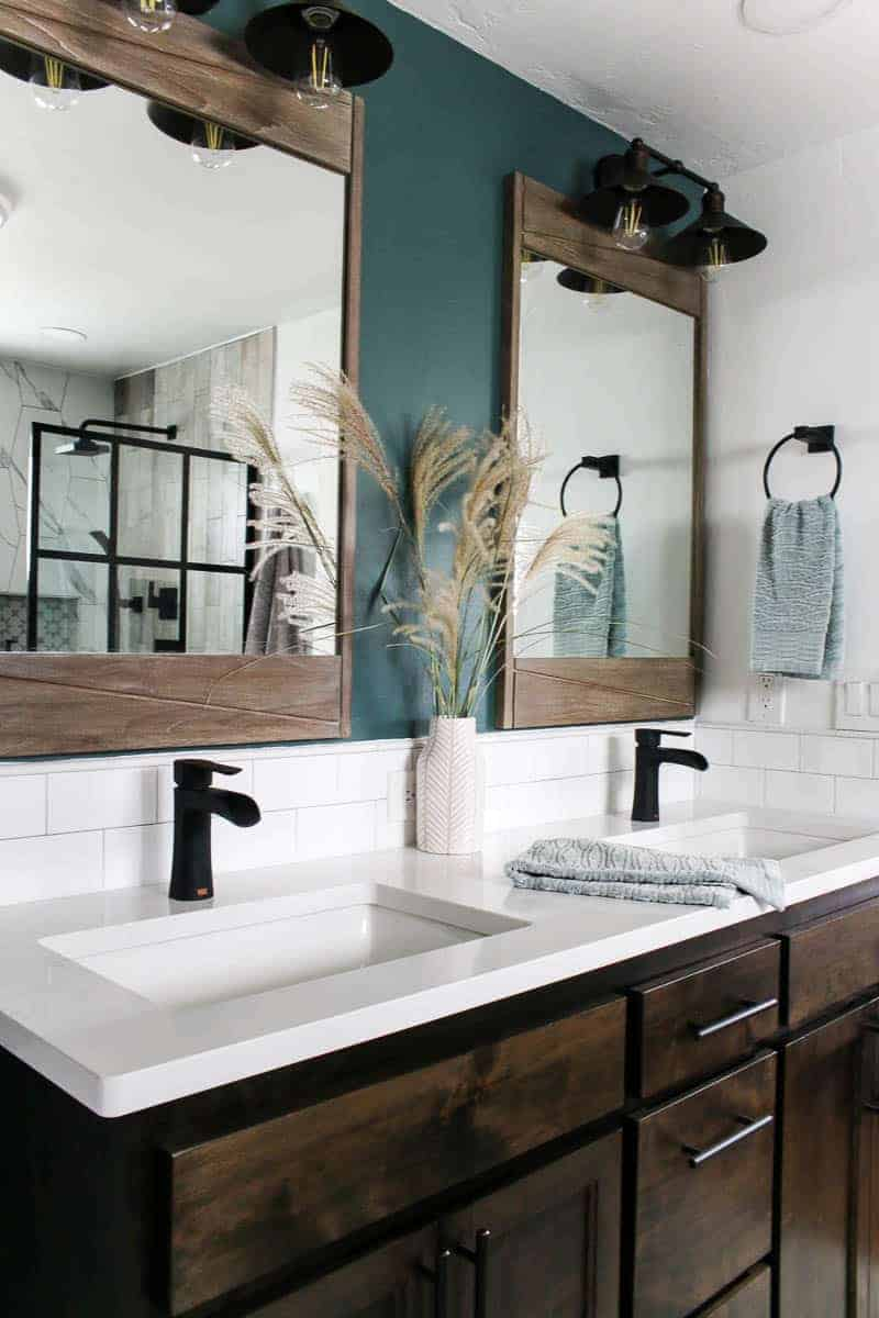 Farmhouse vanity area with dual sinks, black faucets, white quartz countertop and subway tile backsplash, green accent wall, large teak wood mirror and farmhouse style vanity lights