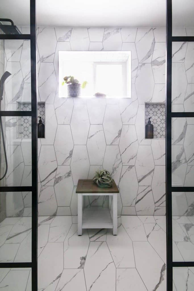 Modern looking shower with bright window. White marble tiles and black shower heads with black paneled windows and white table.