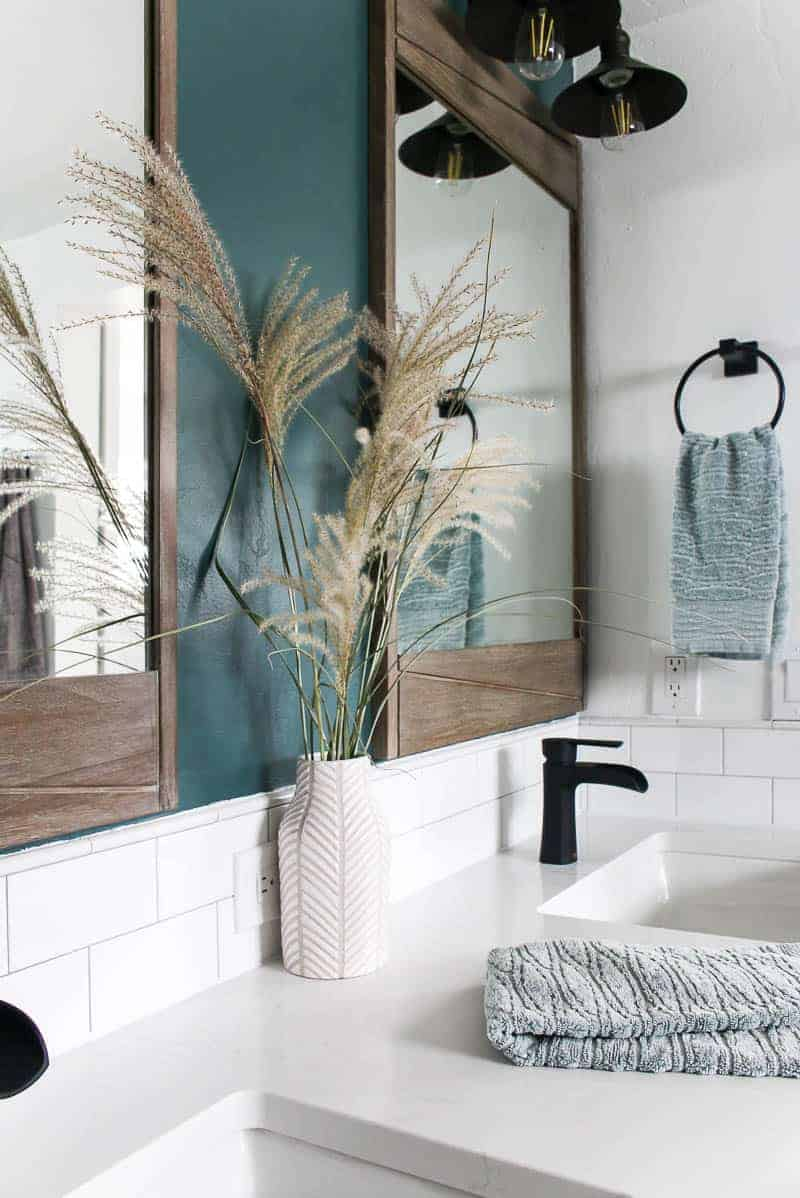 bathroom picture with dried grass in vase and wooden mirror above vanity with black faucets, white quartz countertop with white subway back splash