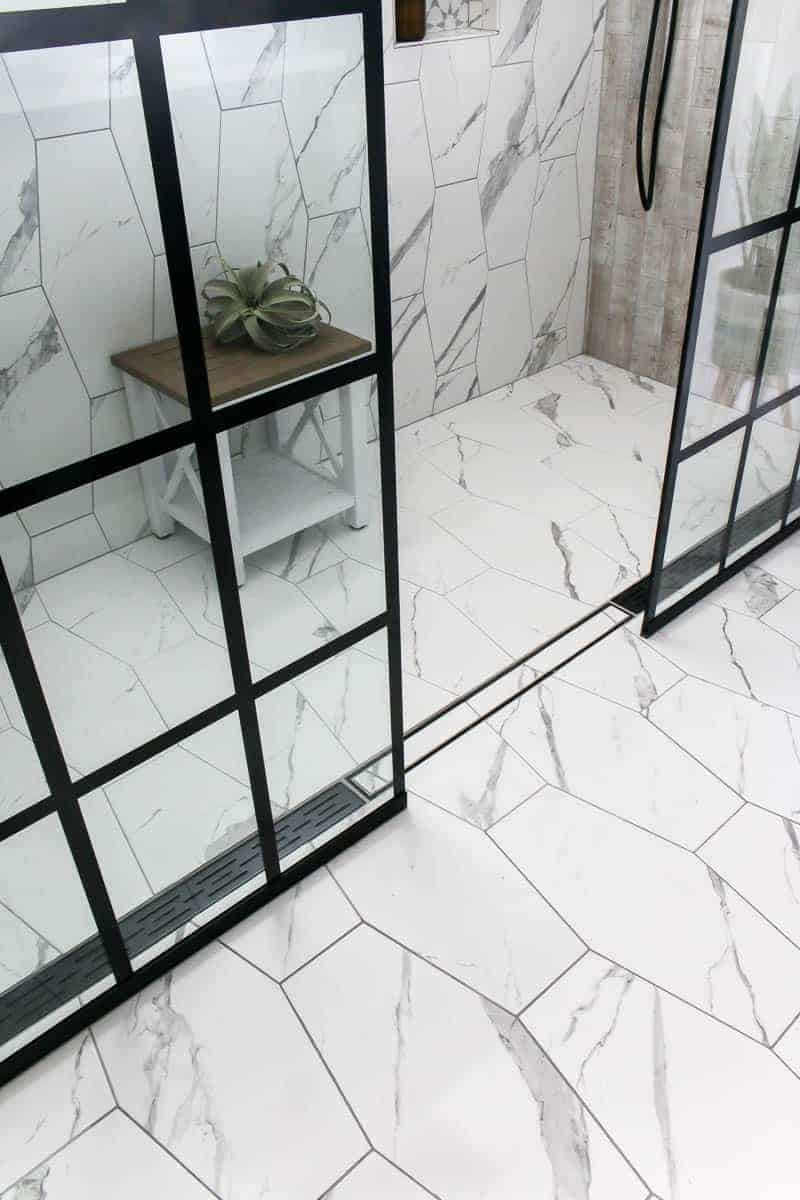 Modern bathroom flooring with marble looking white hexagon large format tile on floor and back wall with linear drain in shower for a seamless design