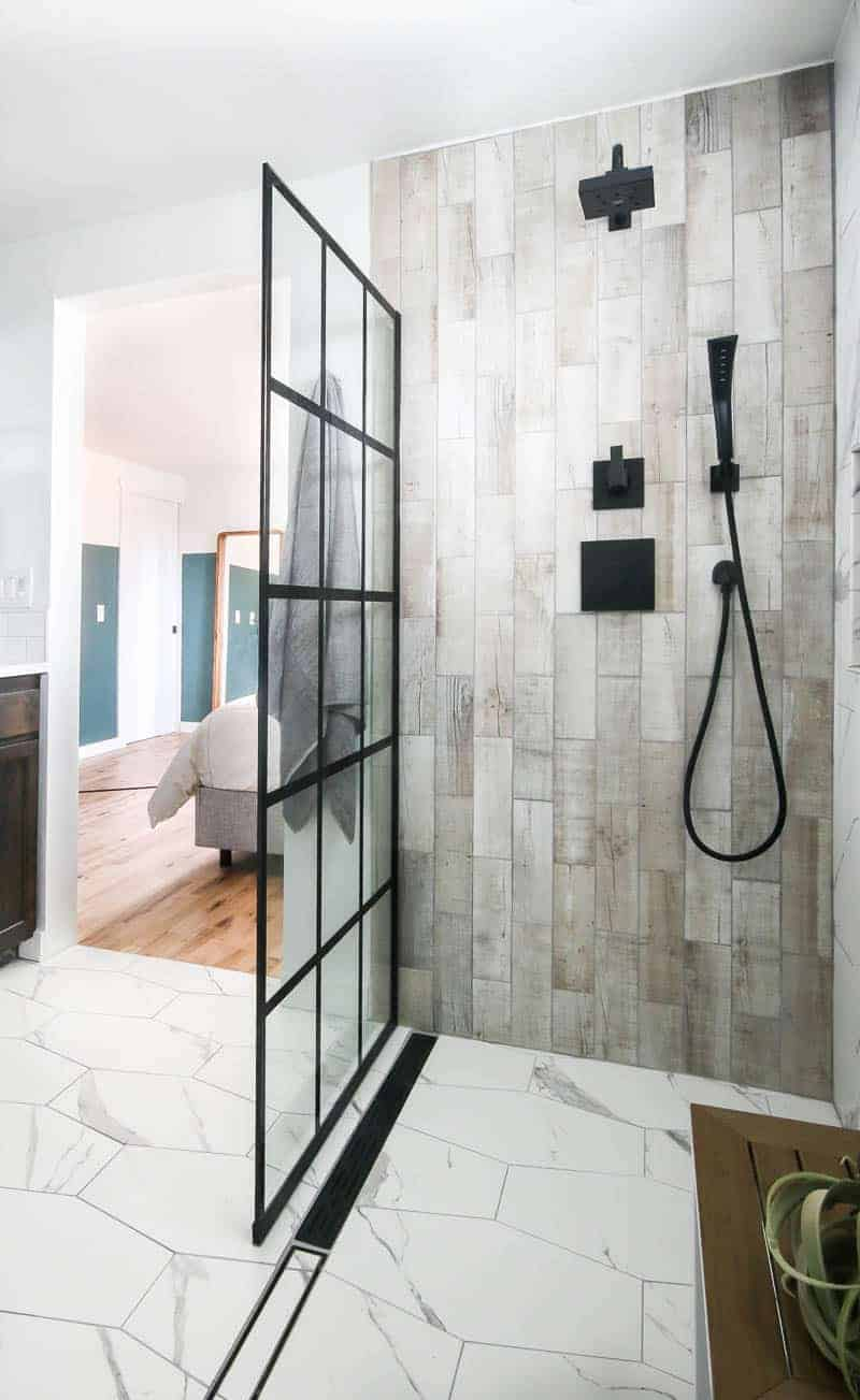 Shower area with wood look tile on sides, black faucet and shower head and white hexagon tile on the floor with windowpane shower door panel. The door way open to the bedroom in the background