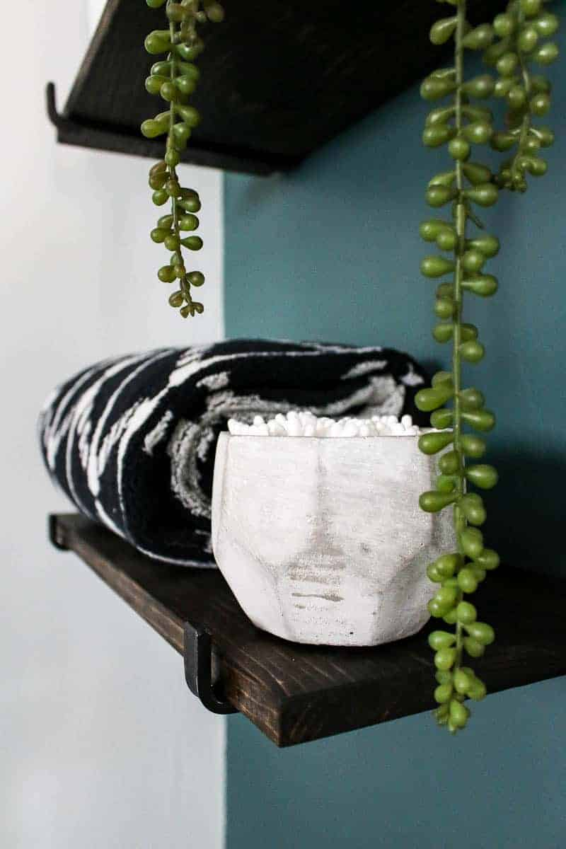 Floating wood shelves with towels folded on shelf, concrete bowl with Q-tips, and some plant accent