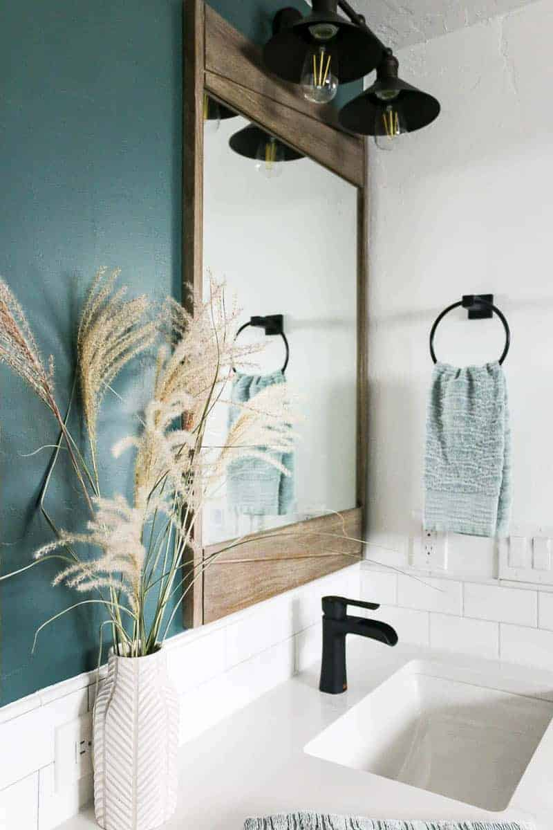 Vanity area in master bathroom with modern farmhouse style showing dark green accent wall, large teak wood mirror, barn vanity light and a towel ring holding green textured hand towel with white sink, countertop, blacksplash and black sink faucet