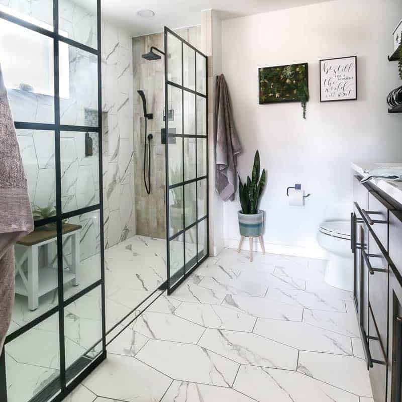 Modern boho looking bathroom with white tile floors and showers with dark wood vanity and black panel windowpane shower doors