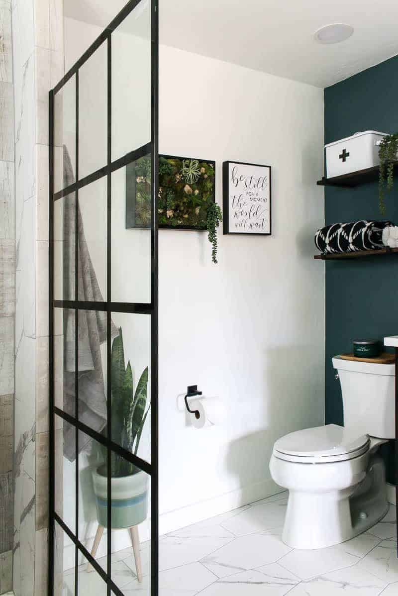 Toilet area with frames on the wall and hanging shelves with first aid kit and bath towel on shelf