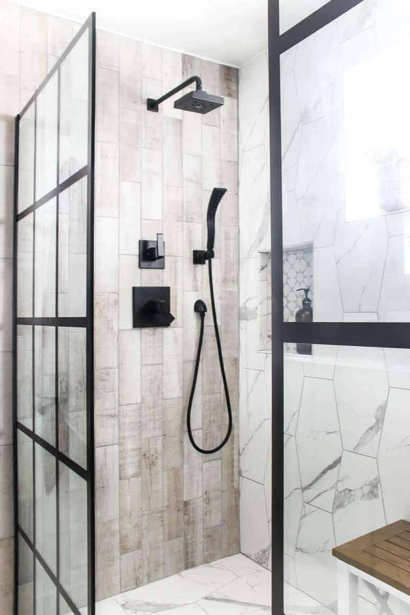 Shower design with black shower doors and shower head with marble hexagon tile and wood look tile.