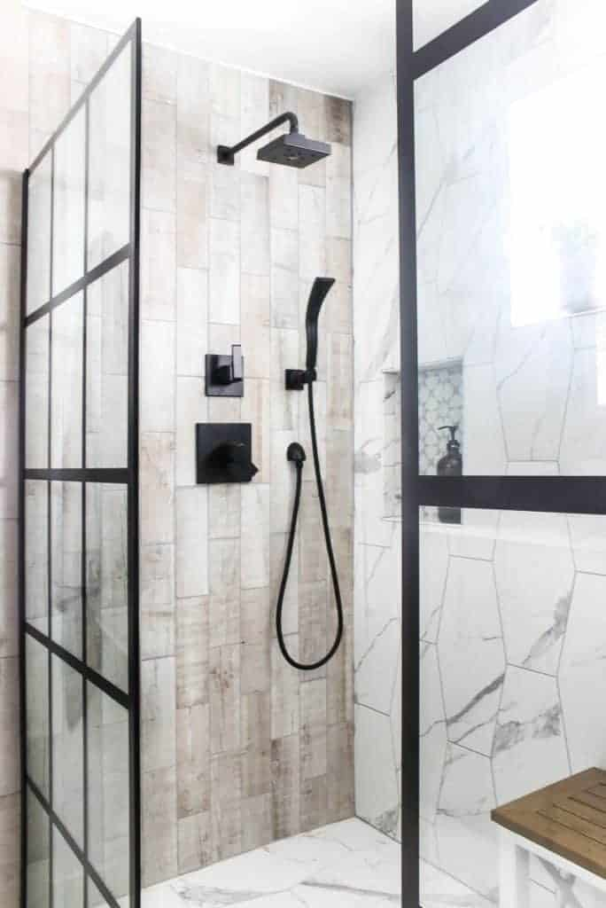 Modern looking shower with white hexagonal marble tile on the right and wood look rectangle tile on the left with a black shower head and windowpane fixed shower door panels.