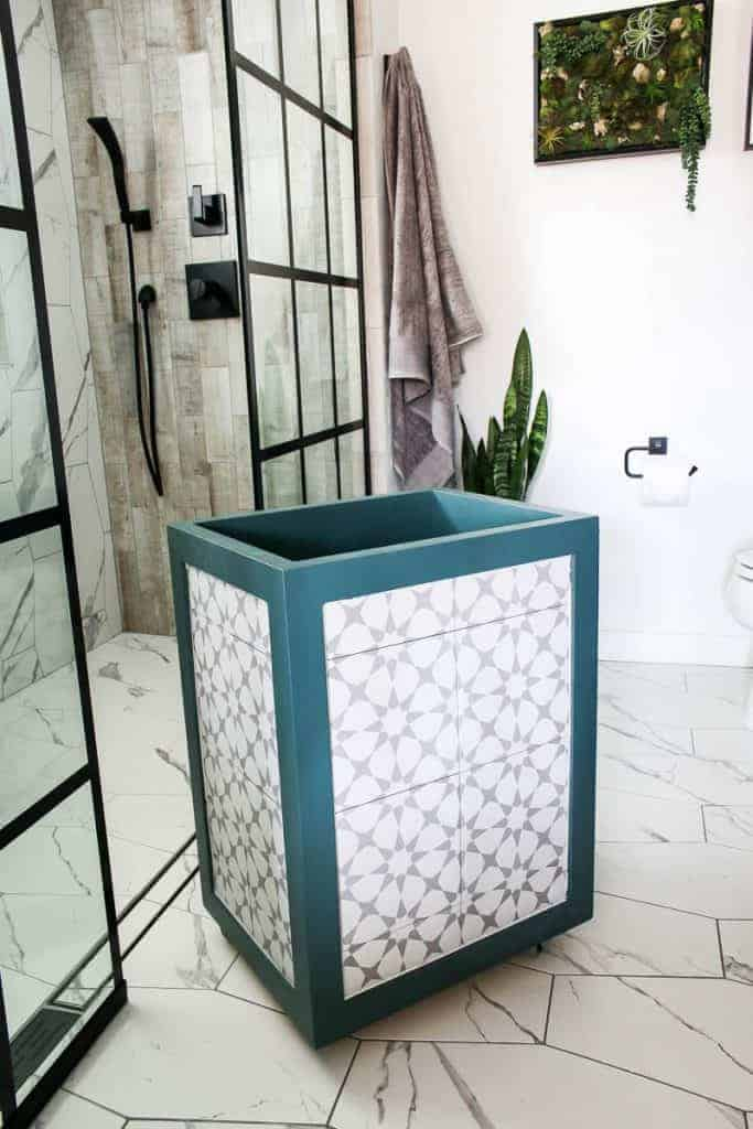 Laundry hamper with teal edges with gray and white tile inlay sitting in a white bathroom with tile marble floors and black shower window panels