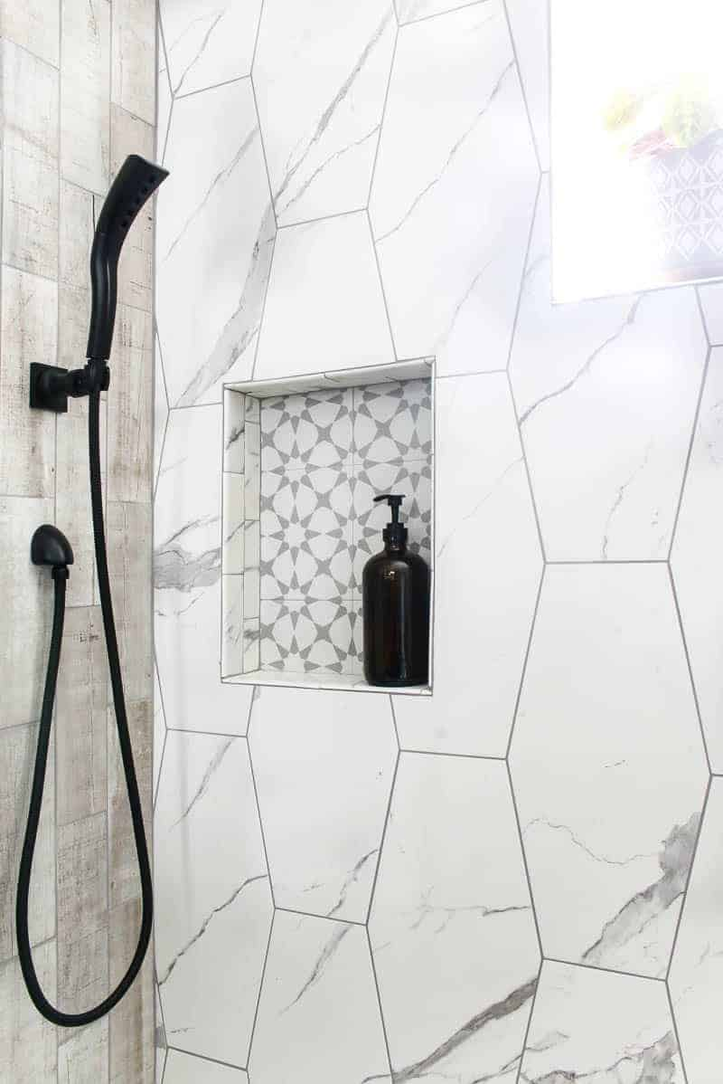 Amber glass soap holder with pump sitting in shower niche in luxurious shower with large white hexagon tile and wood look tile with black hand shower shown on left