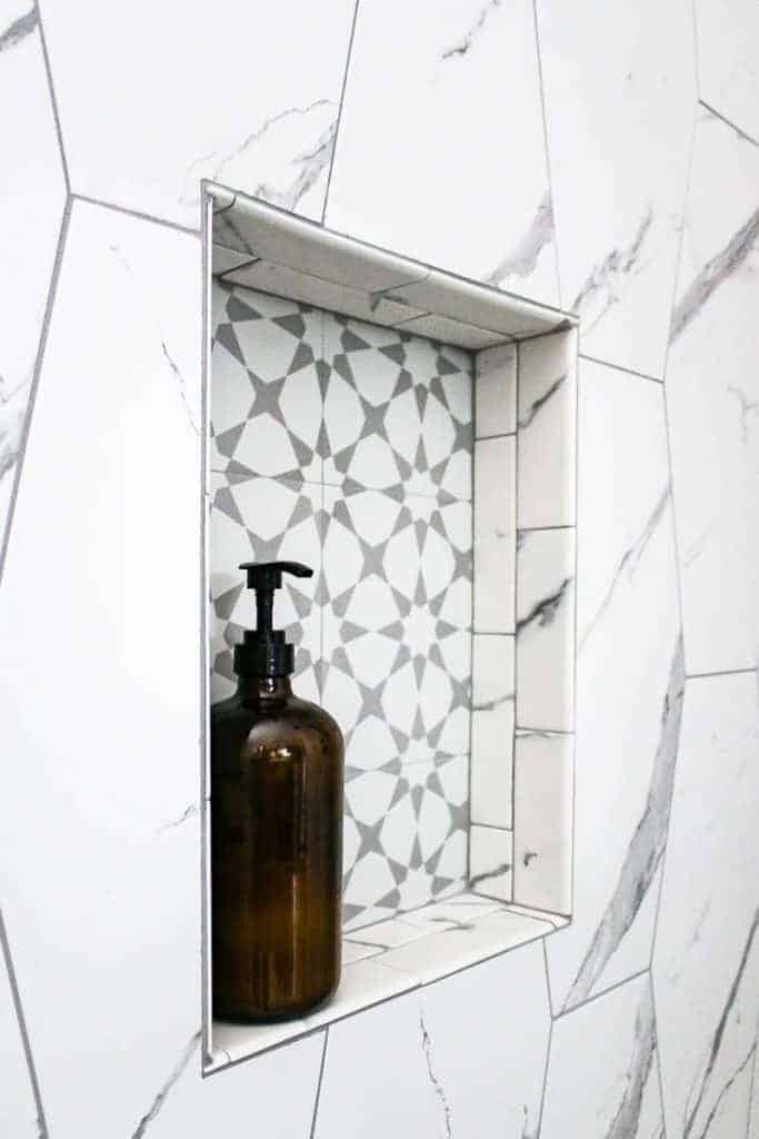 Shower shelf with gray accent tile in back and marble tile around edge of shower shelf and on the shower walls with amber glass bottle on shelf