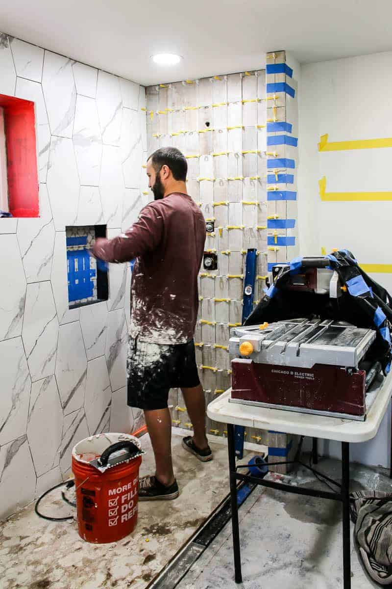 Man attaching the tiles in shower with tile saw set up in bathroom