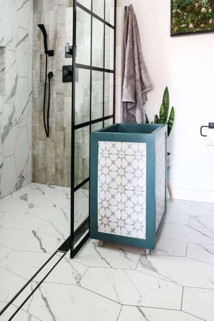 Laundry hamper with gray and white tile inlay in a corner of a white wall bathroom with back shower window panels and marble tile floors