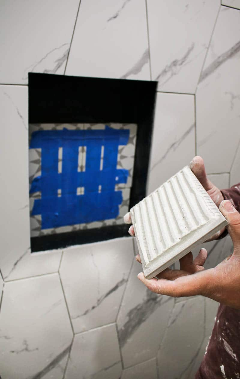 Man holding a tile ready to be installed on the bathroom wall