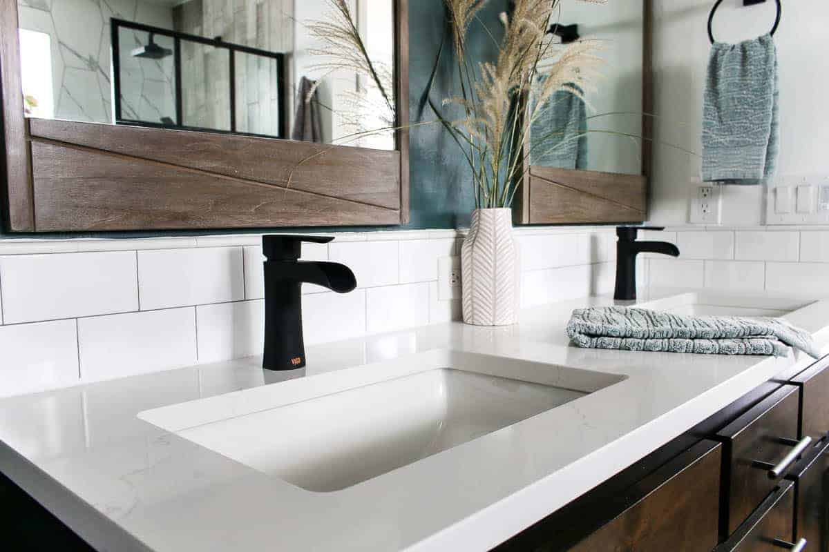 White quartz countertop on bathroom vanity with two sinks with black faucets and wooden mirrors