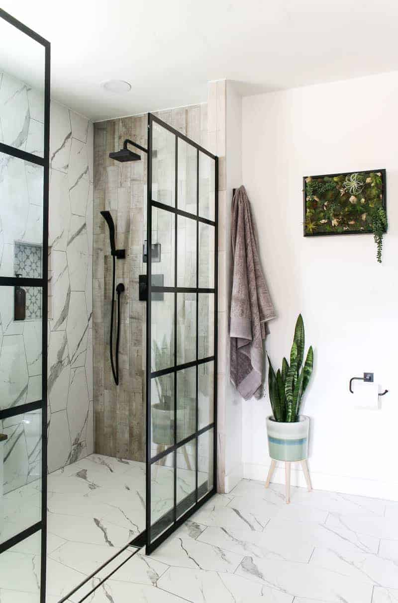 New look of the shower area with black shower system, indoor plant, hanging towels and a wall frame decor with fake succulents
