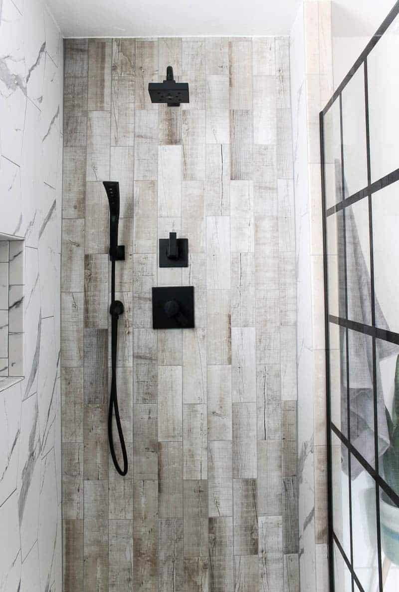 Shower area with wood look tile and black shower head and faucet