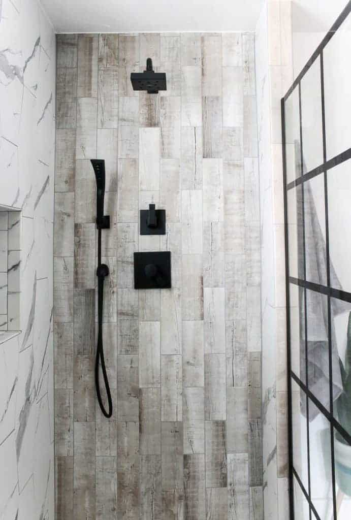 Modern shower with marble hexagonal tile on the left and beige rectangle shower in the center with black shower heads. On the right is black paneled window panes for shower doors