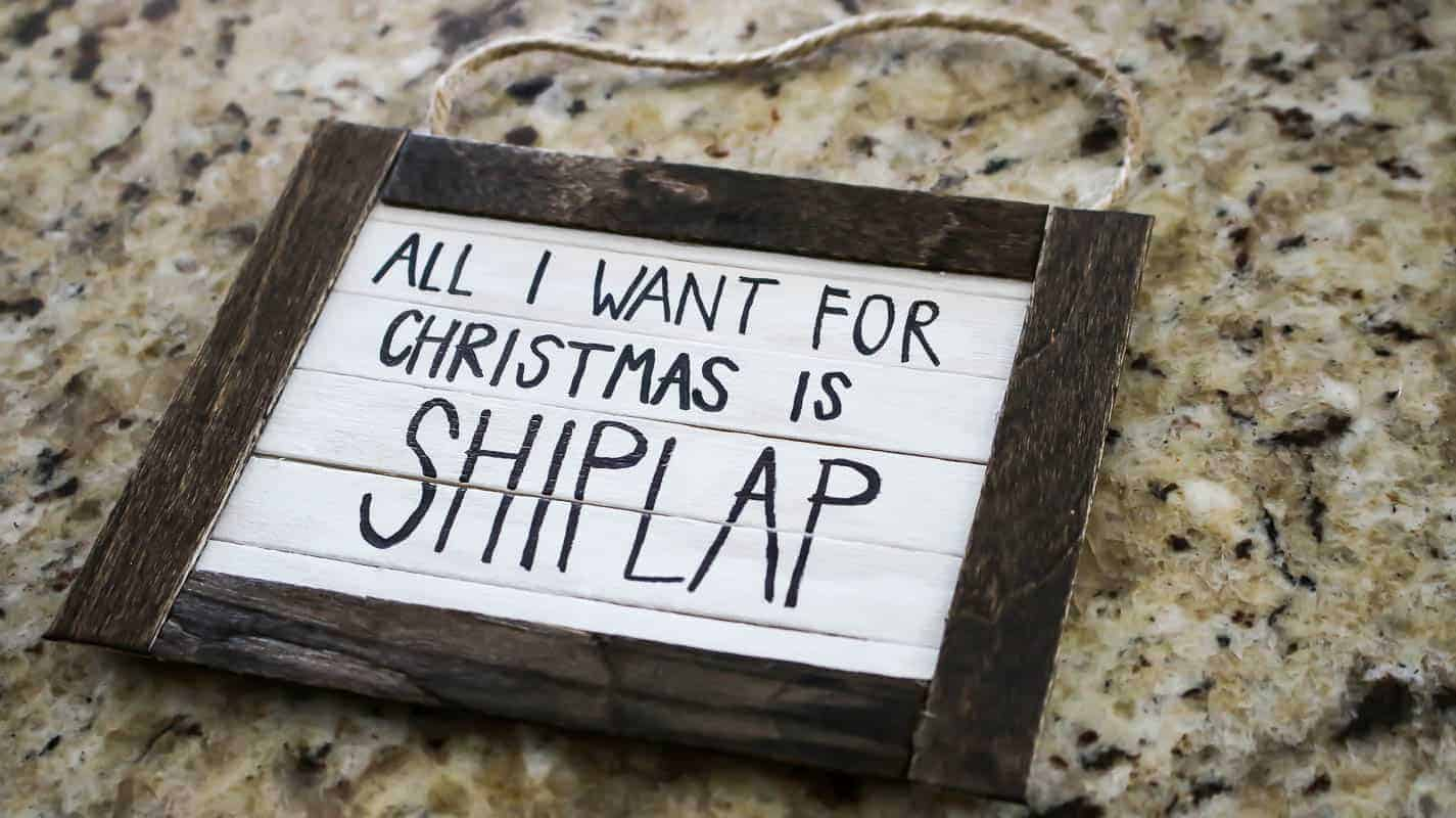 Finished project of the handmade Christmas ornament with text inside that says All I Want For Christmas is Shiplap