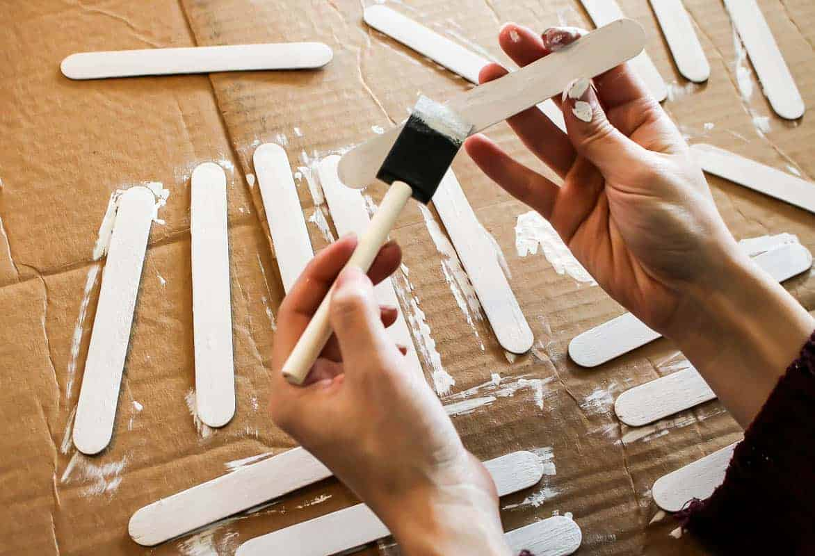 Painting a Popsicle stick with white paint using a foam paint brush and a few more painted Popsicle sticks placed on the carton