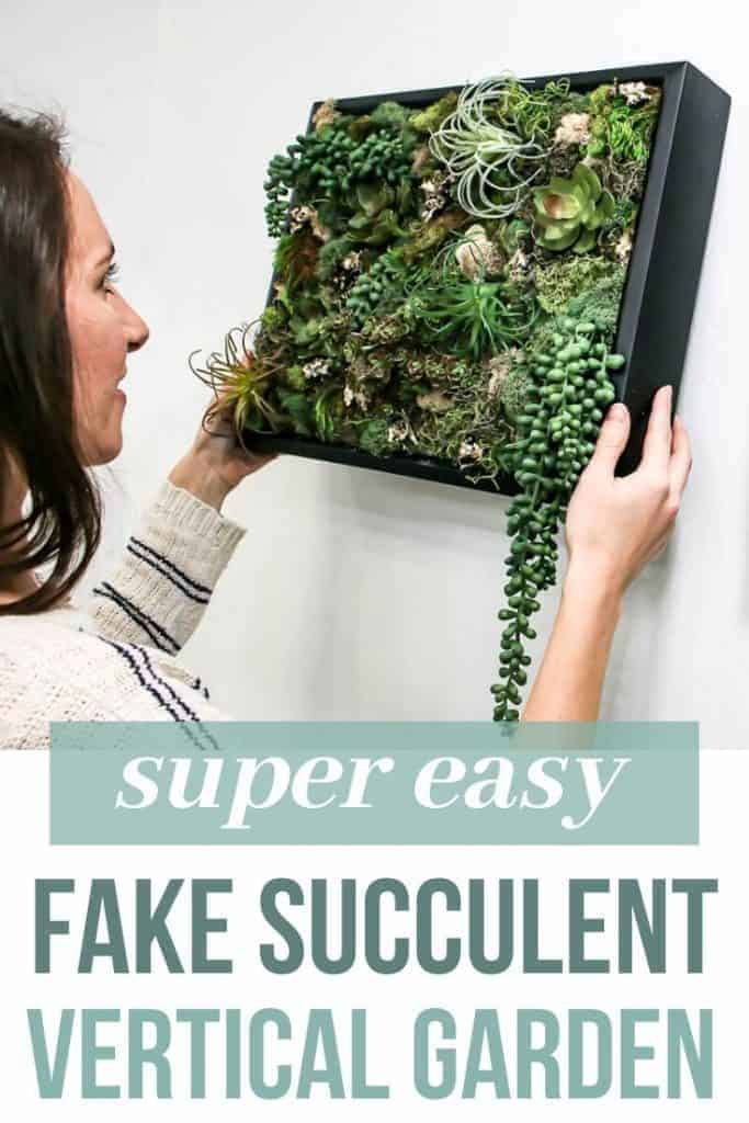Woman hanging succulent wall decor in black frame on the wall in bathroom with text overlay that says super easy fake succulent vertical garden