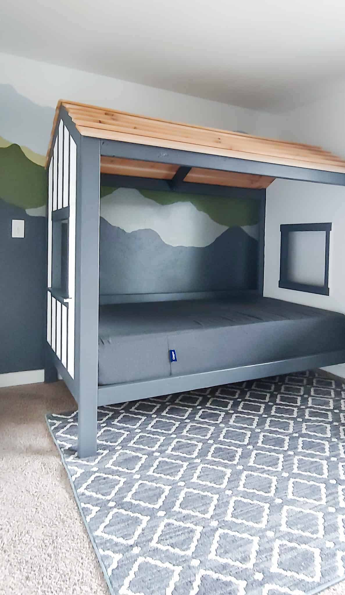 Full view of the DIY cabin bed pushed closely to the wall with mountain mural and the farmhouse carpet