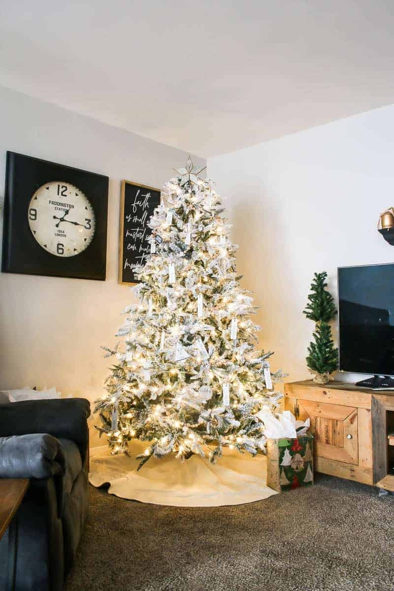 Farmhouse Christmas tree standing at the corner of the living room beside the barn styled TV cabinet, television and wall sign and on the left side of the wall is a clock and printable wall decor frame