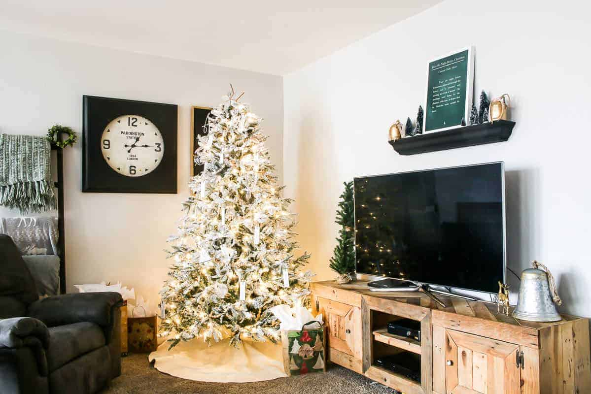 Farmhouse Christmas tree with reclaimed tree topper, diy wooden ornaments with personalized words and barn wooden angel - standing at the living room beside the farmhouse TV rack and shelf on top with Christmas sign on top, Christmas trees and Christmas bells while on the other side of the wall is the black wooden clock and the printable wood sign frame