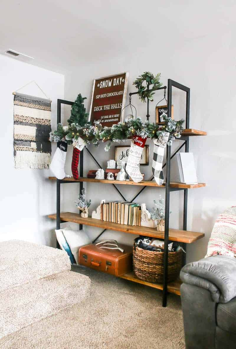 Four layered shelf with Snow Day Christmas sign, ornament and farmhouse decors on the first shelf, on the second shelf are Christmas garlands, Christmas socks, mini Christamas village with DIY Christmas and personalized family sign, third shelf contains vintage books and Christmas decors and the last shelf has throw pillows, vintage suitcase and a basket.