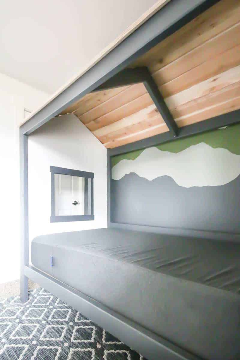 Other side of the cabin bed with gray sheets, wooden roof, white wall on the end with a tiny window like a tiny cabin