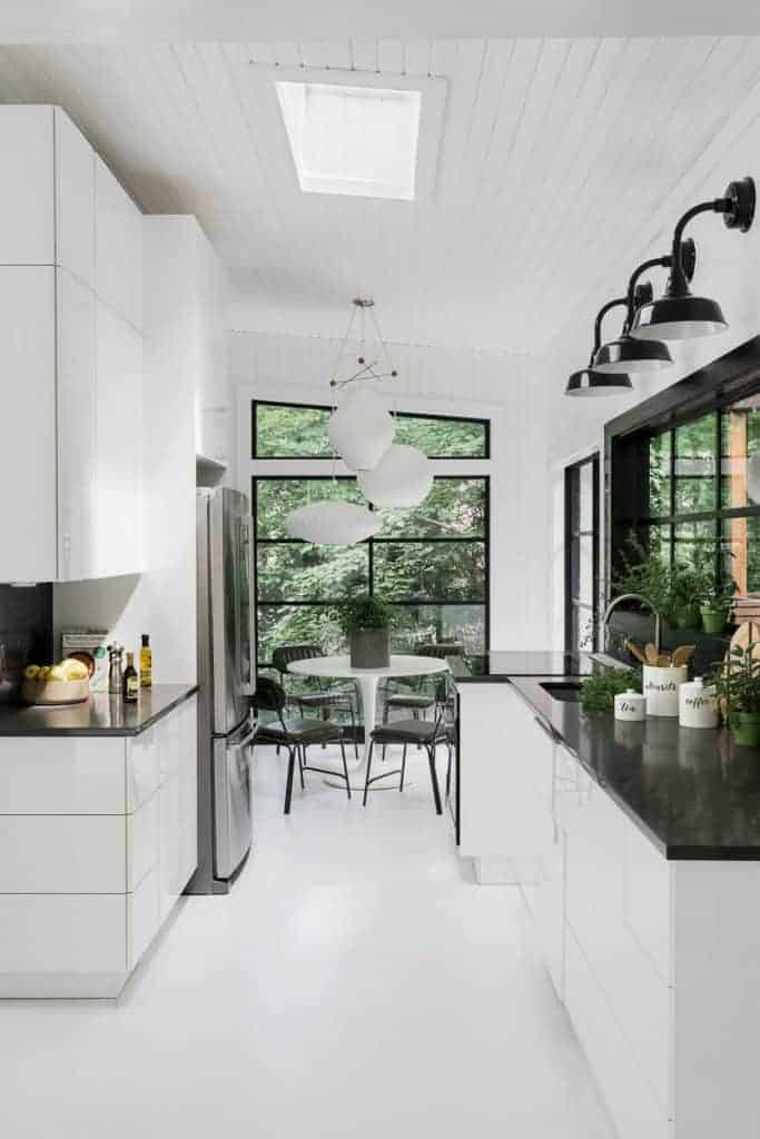 Modern White kitchen with white cabinets, floors and walls with black accents and counter tops and a skylight.