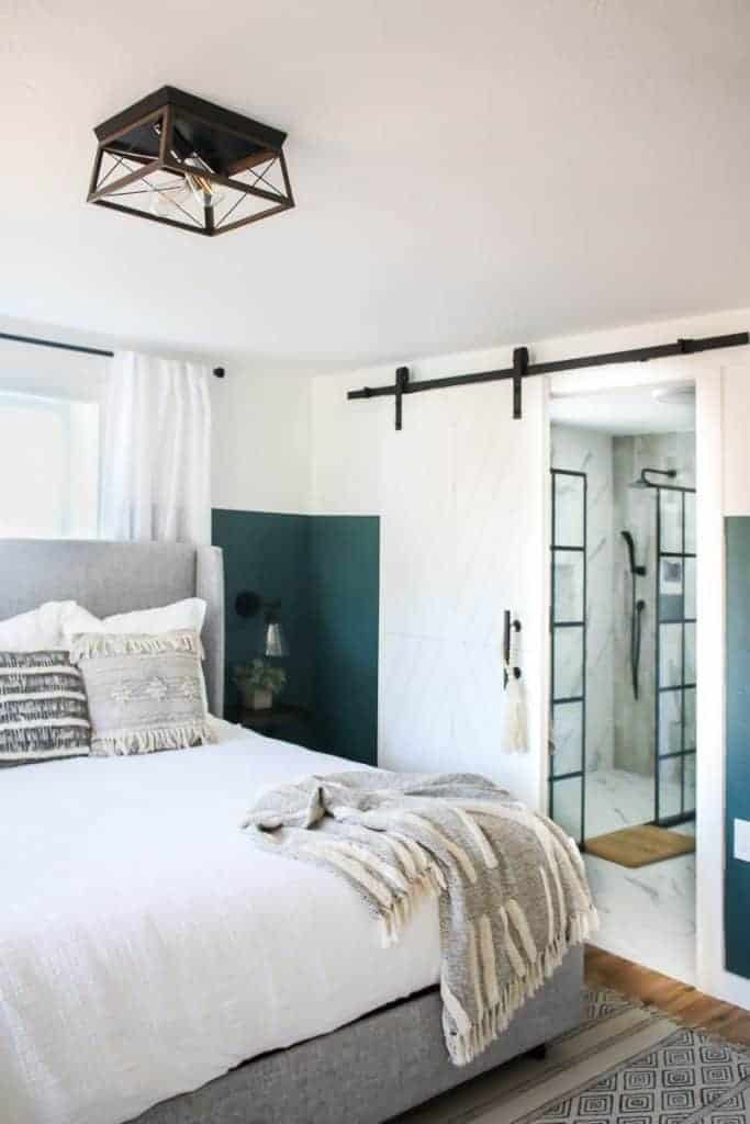 View on the other side of the modern boho bedroom showing the barn door straight to the bathroom, barn chandelier, wooden nightstand with indoor plant on top and the side of the bed.