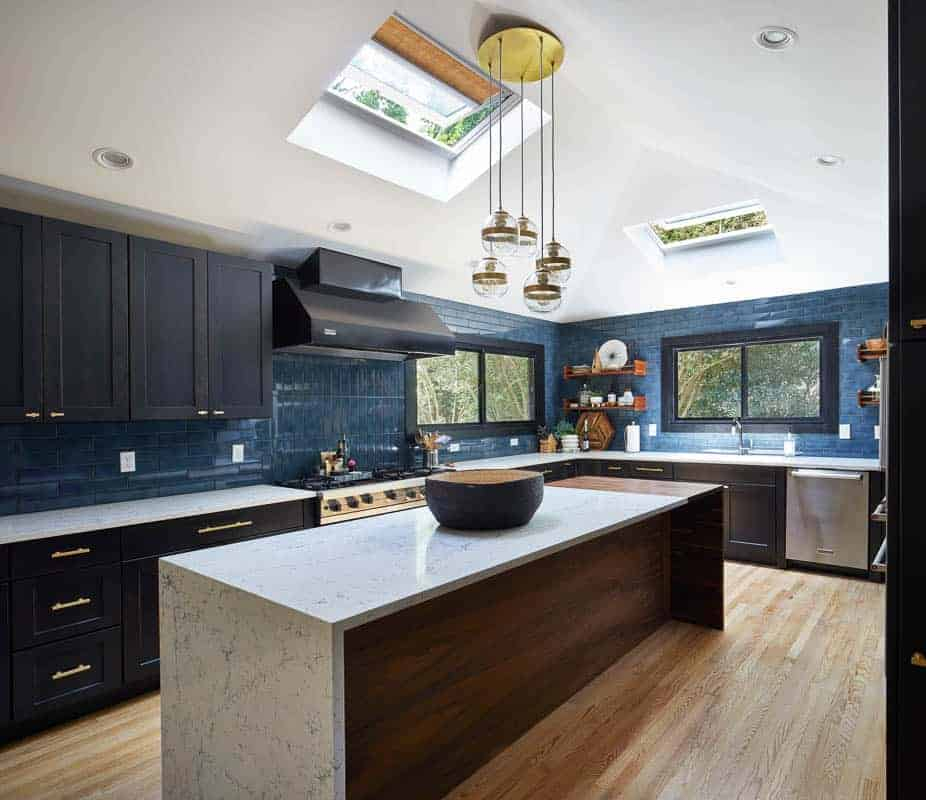 Dark blue modern kitchen with dark cabinets and dark appliances with a wood kitchen island with white counter tops, brightened with a skylight