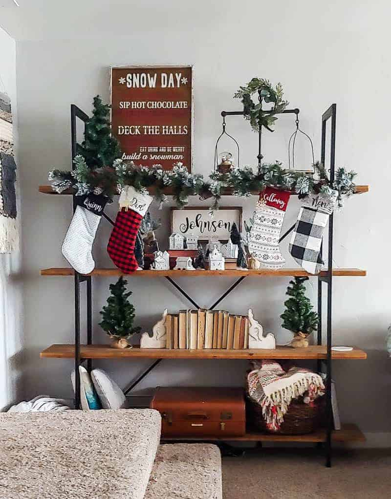 Front view of the shelf with Christmas sign, wreath, garland, personalized Christmas socks, Christmas village with the mini Christmas trees, books, throw pillows, suitcases and basket