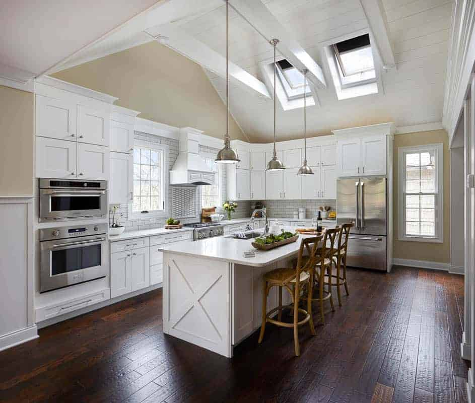 Farmhouse styled kitchen with skylights and vaulted ceilings. White cabinets and counter tops with metal appliances and dark wood floors.