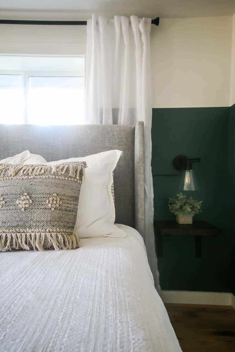 Half view of the best and bedroom window with the hanging nightstand and night lamp on the side of the bed.