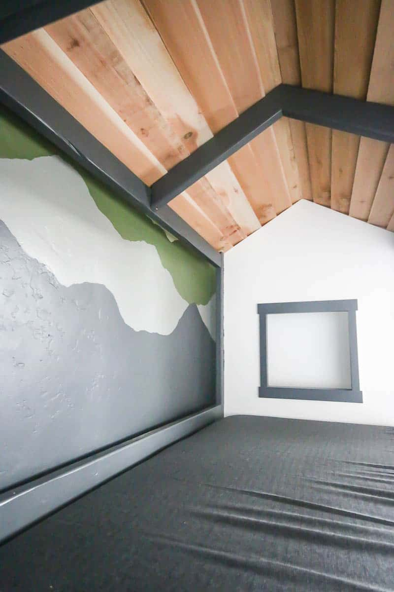 Inside view of the cabin bed showing wooden roof, tiny window at the end and the bed with gray sheets pushed closely to the wall with mountain mural