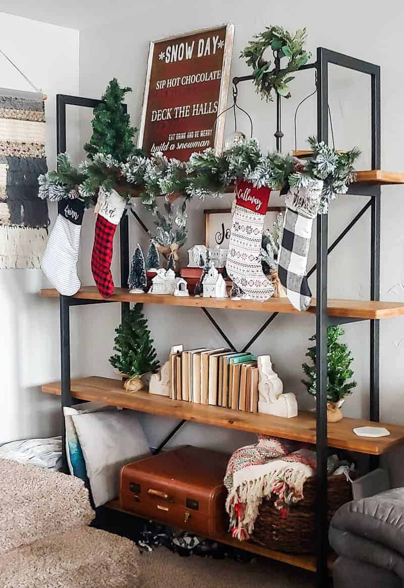 Shelf with Christmas decorations including Christmas stockings, Christmas sign, wreath garlands, White Christmas Village, mini Christmas trees, books, suitcase and throw pillows and basket