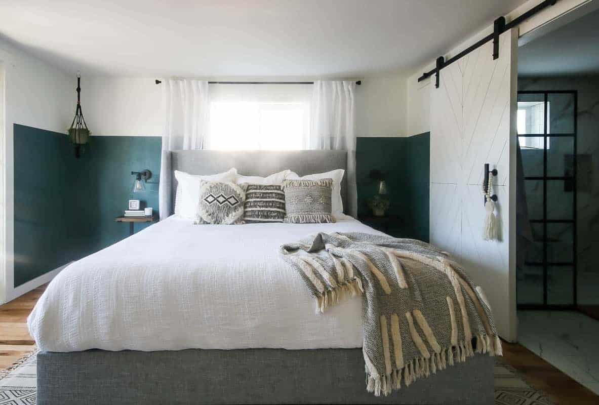 Front view of the modern boho bedroom showing the bed with boho trow pillows and blanket, hanging night stand on each side with indoor plant and night lap, barn door straight to the bathroom and the haning plant on the left side of the modern boho bedroom